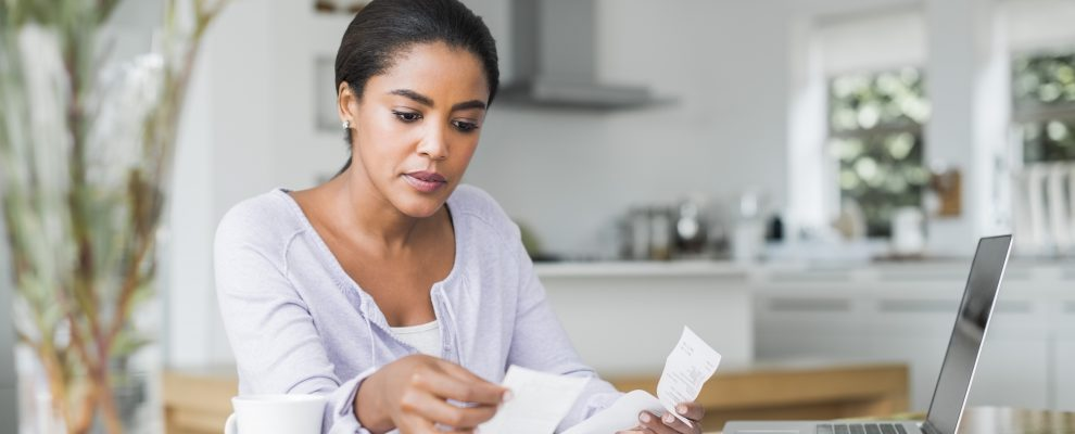 Mid adult woman reading bills while making online payment at home